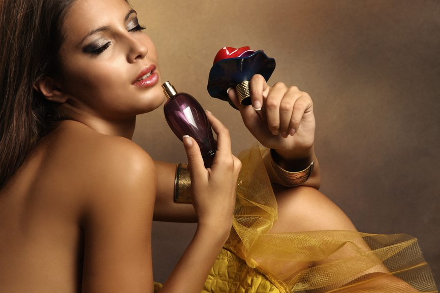 Elegant sensual young woman holding perfume, golden tones, small amount of grain added