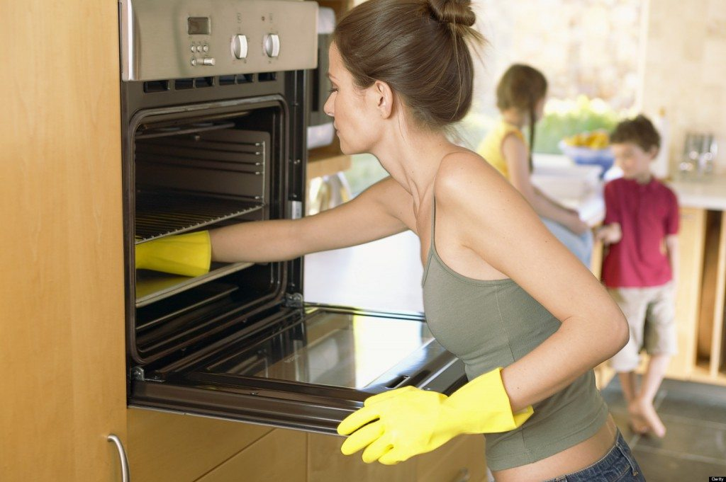 Woman cleaning oven --- Image by © Lou Cypher/Corbis
